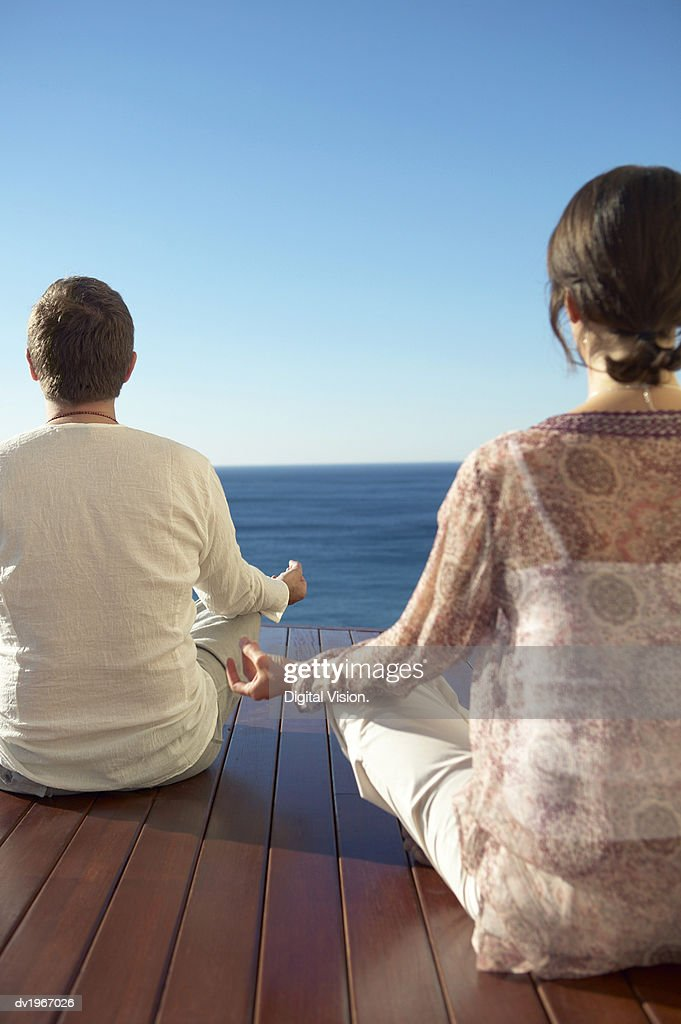 Rear View of a Man and Woman Sitting on Decking by the Sea, Meditating in the Lotus Position : Stock Photo