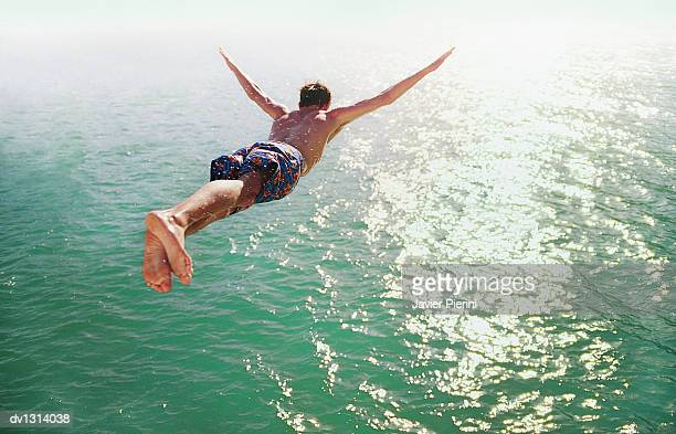 rear view of a man diving into the sea - coraggio foto e immagini stock