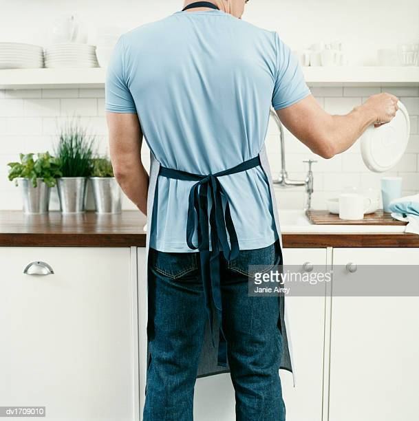 Rear View of a Man Doing the Washing Up