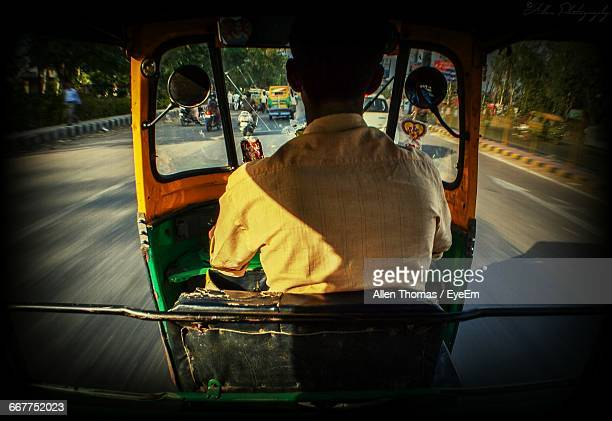 rear view of a man driving auto rickshaw - auto rickshaw stock pictures, royalty-free photos & images