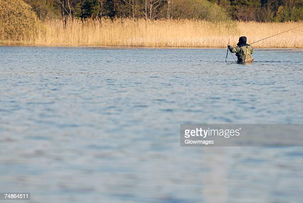 Rear view of a man fishing in the river