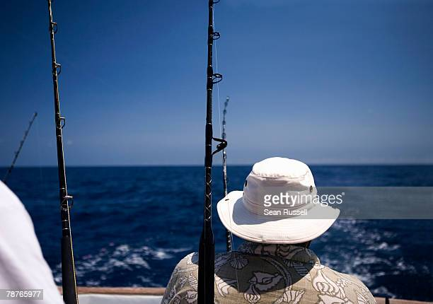 rear view of a man fishing on a boat - big game fishing stock photos and pictures