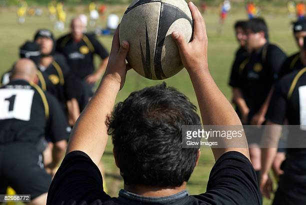 rear view of a man holding a rugby ball - ラグビー場 ストックフォトと画像