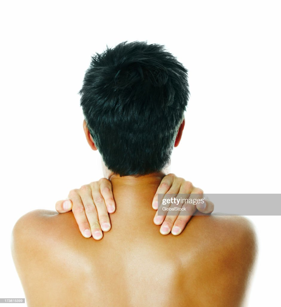 Rear view of a man holding his shoulders : Stock Photo