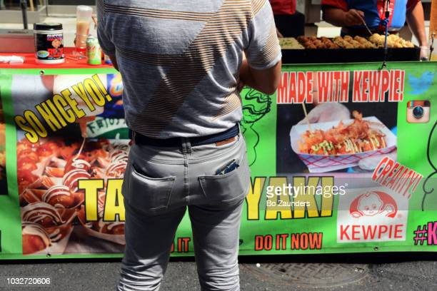 Rear view of a man in front of a Japanese food stand, at a street fair in NYC.