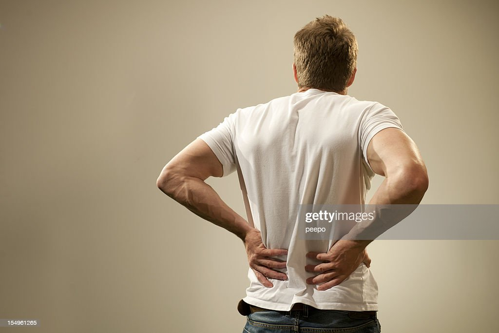 Rear view of a man in t-shirt holding his back in pain. : Stock Photo