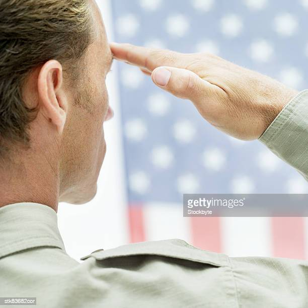 Rear view of a man in uniform saluting the American flag