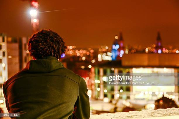 Rear View Of A Man On Balcony Looking At City At Night