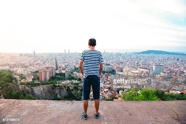 Rear view of a man ovelooking Barcelona from a viewpoint at sunrise