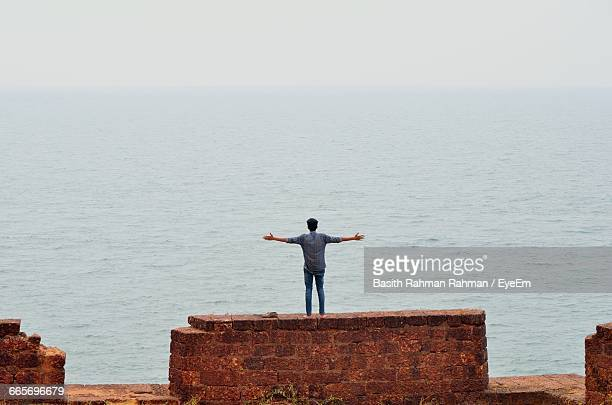 Rear View Of A Man Overlooking Calm Sea