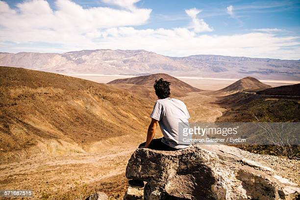 Rear View Of A Man Overlooking Rocky Landscape