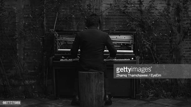 Rear View Of A Man Playing The Piano