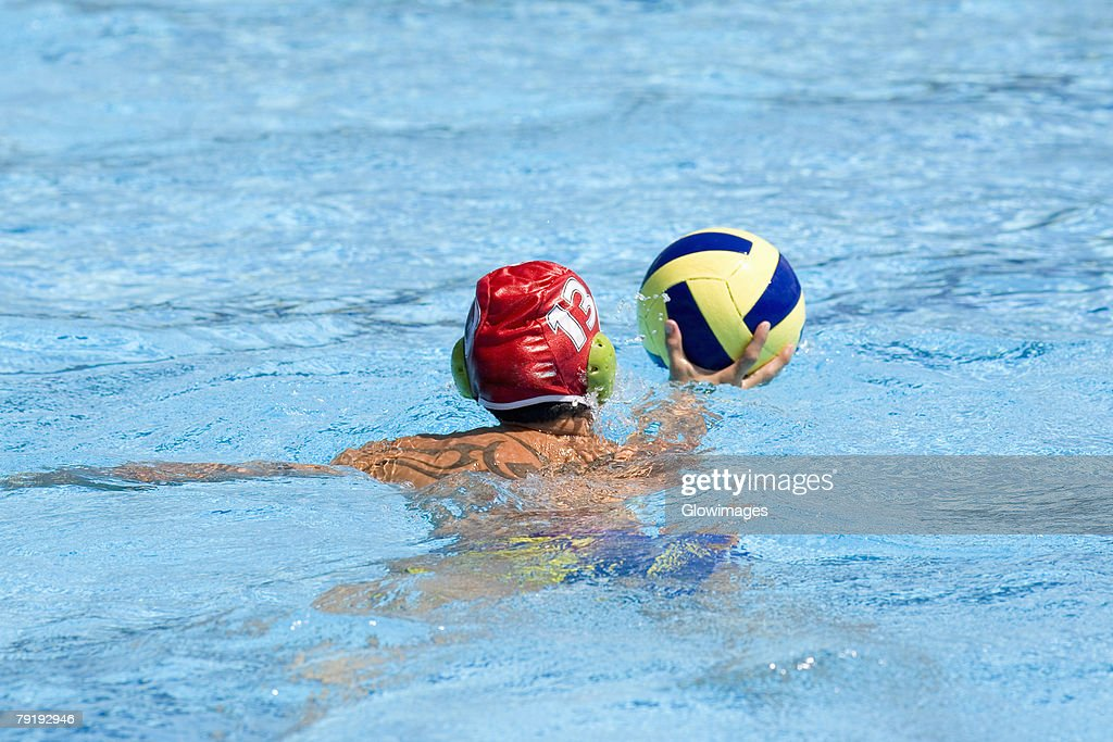 Rear view of a man playing water polo in a swimming pool : Foto de stock