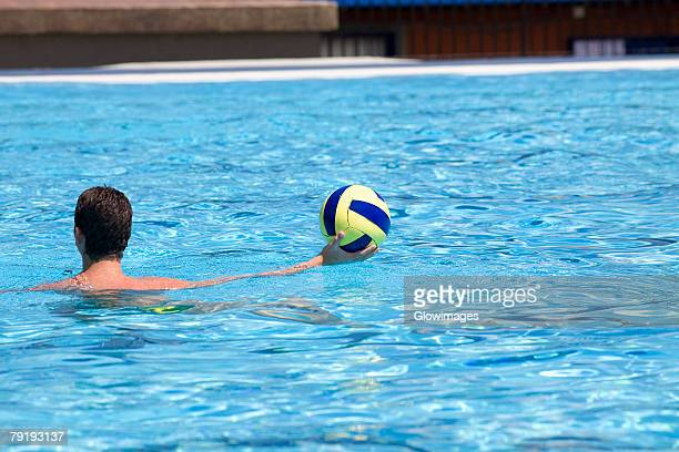Rear view of a man playing water polo in a swimming pool