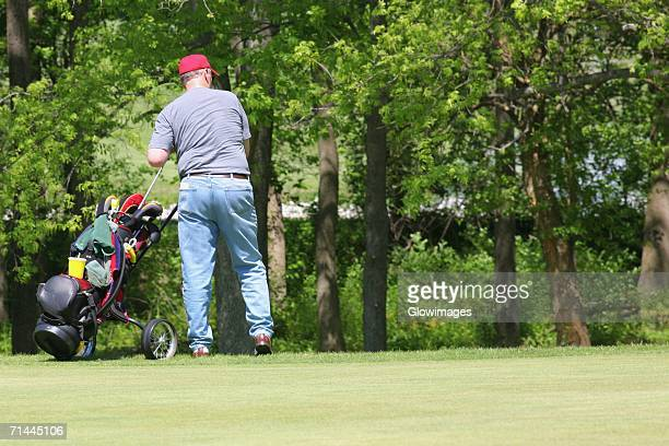 Rear view of a man pulling a golf bag on a trolley