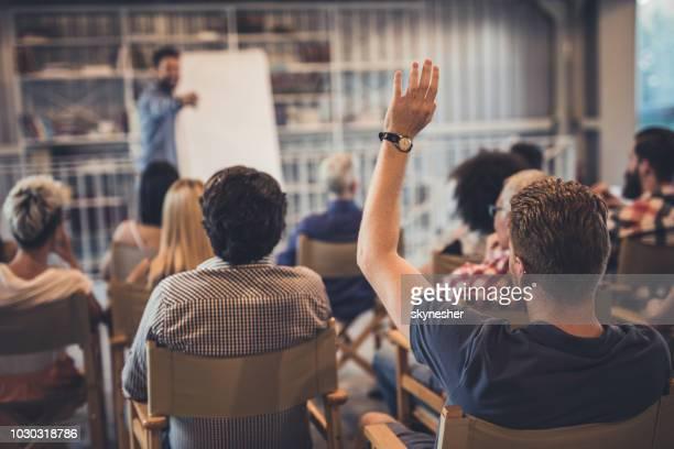 vista traseira de um homem levantando o braço sobre um seminário. - curso de treinamento - fotografias e filmes do acervo