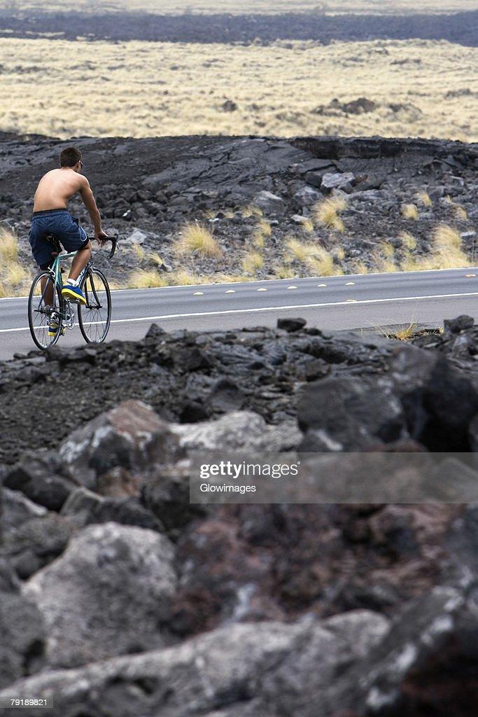 Rear view of a man riding a bicycle on the road, Kona Coast, Big Island, Hawaii Islands, USA : Foto de stock