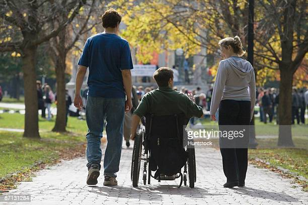 rear view of a man sitting in a wheelchair with a man and a woman walking to a war protest - politische versammlung stock-fotos und bilder