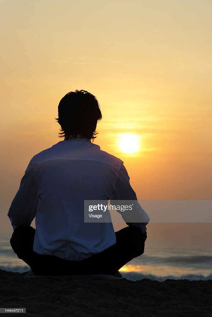 Rear view of a man sitting on a beach : Stock Photo