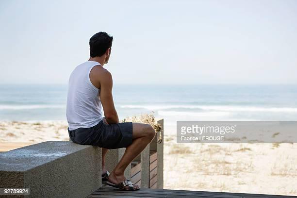 rear view of a man sitting on a boardwalk - débardeur photos et images de collection