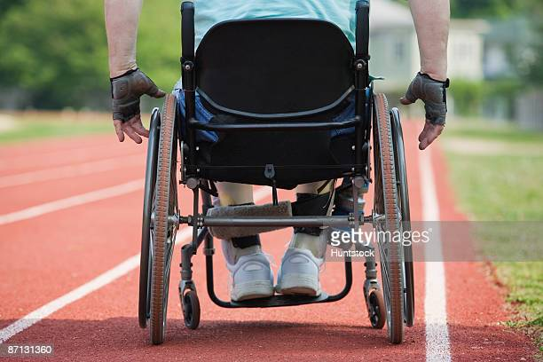 Rear view of a man sitting on a wheel chair on a race track