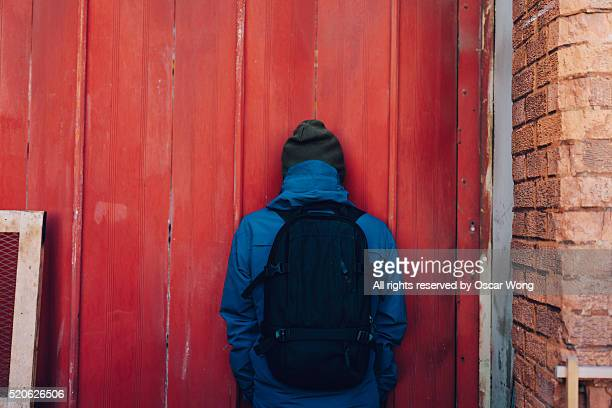 Rear view of a man standing against red wall
