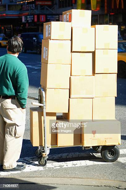 Rear view of a man standing near a push cart with cardboard boxes