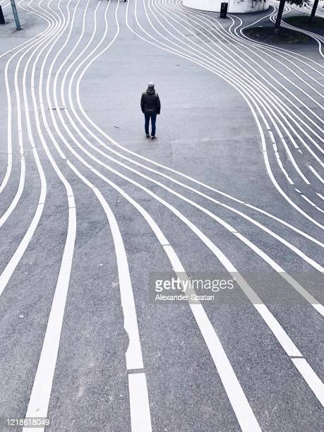 rear view of a man standing on a city street surrounded by parallel lines - einfachheit stock-fotos und bilder