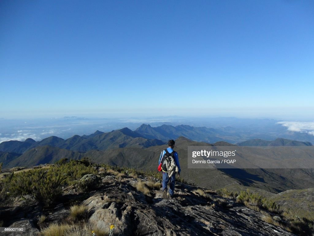 Rear view of a man standing on the mountain : Stock Photo