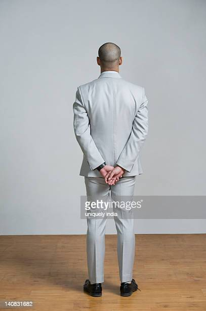 rear view of a man standing - hands behind back stock pictures, royalty-free photos & images