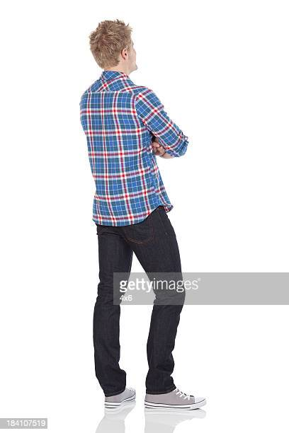 rear view of a man standing with arms crossed - op de rug gezien stockfoto's en -beelden