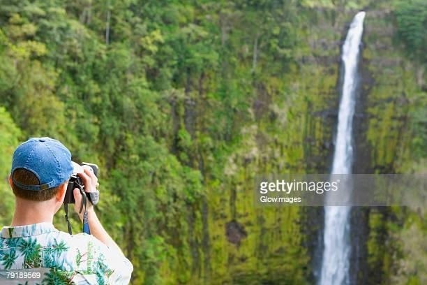 Rear view of a man taking a photograph of a waterfall, Akaka Falls, Akaka Falls State Park, Hilo, Big Island, Hawaii Islands, USA