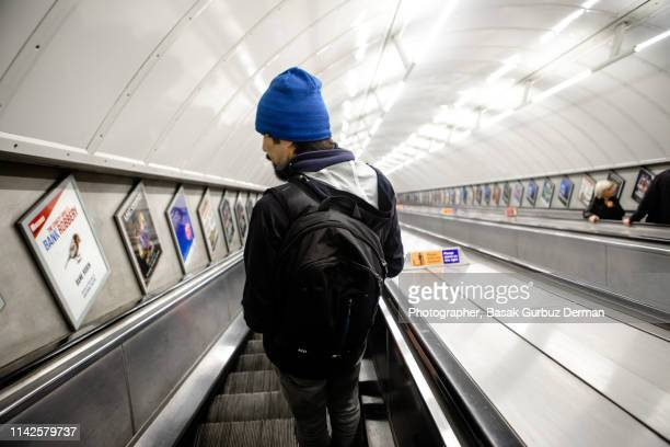rear view of a man traveling on escalator of subway in london - basak gurbuz derman stock photos and pictures