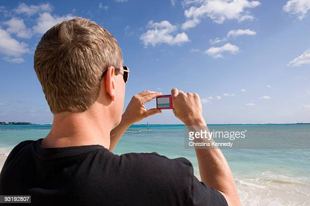 rear view of a man using a digital camera, cable beach, nassau, bahamas, caribbean - cable beach bahamas stock photos and pictures