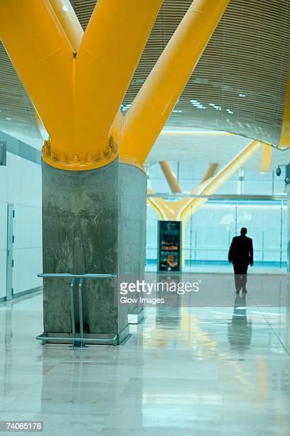 rear view of a man walking at an airport, madrid, spain - advertising column stock-fotos und bilder