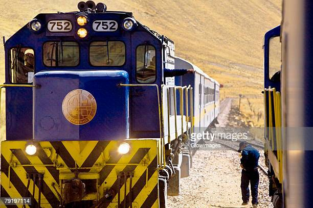 Rear view of a man walking near a train, Puno, Cuzco, Peru
