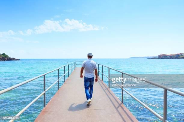 桟橋の上を歩く男の後姿