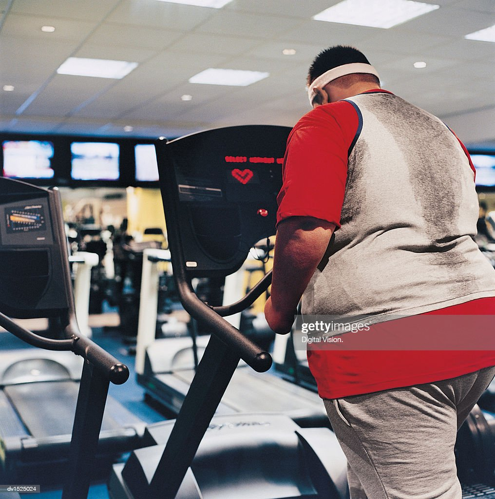 Rear View of a Man Walking on a Running Machine : Stock Photo