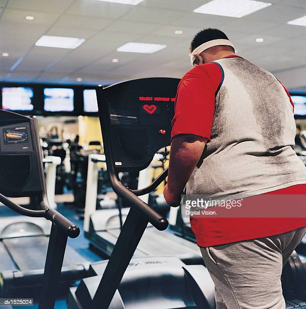 Rear View of a Man Walking on a Running Machine