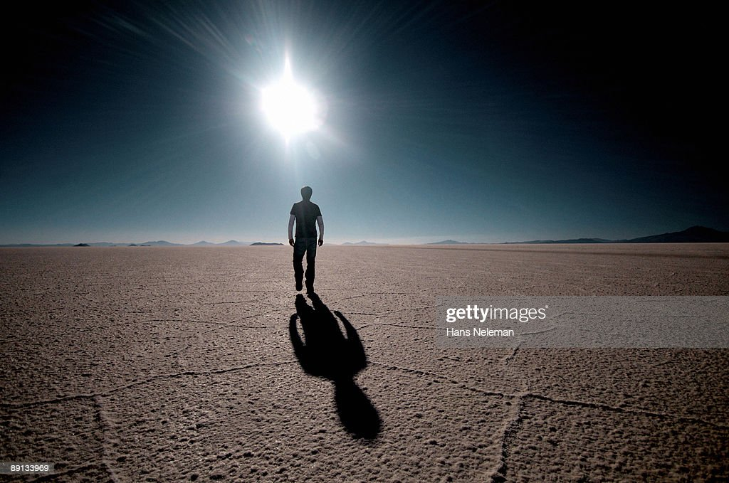Rear view of a man walking on a salt flat, Salar De Uyuni, Bolivia : Stock Photo
