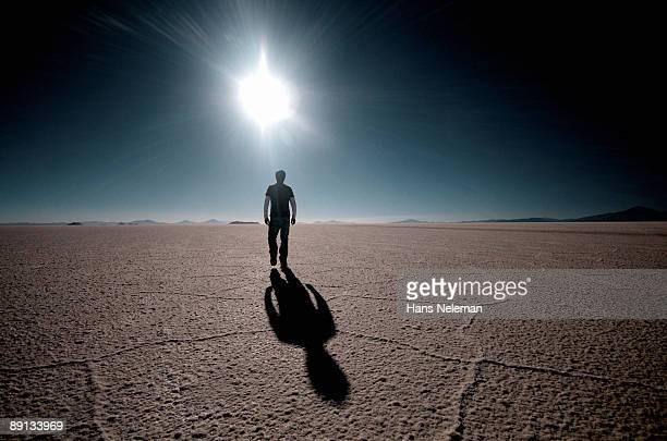 Rear view of a man walking on a salt flat, Salar De Uyuni, Bolivia