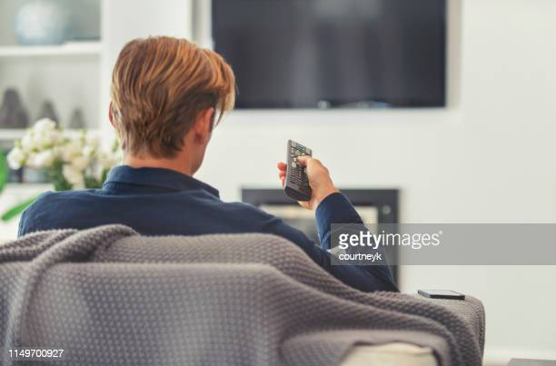 rear view of a man watching television. - looking over shoulder stock pictures, royalty-free photos & images
