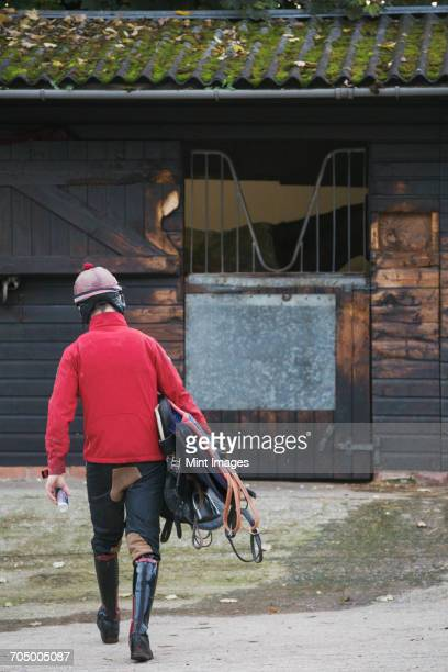 rear view of a man wearing a red jacket and carrying riding gear walking towards a box stall. - riding boot stock pictures, royalty-free photos & images