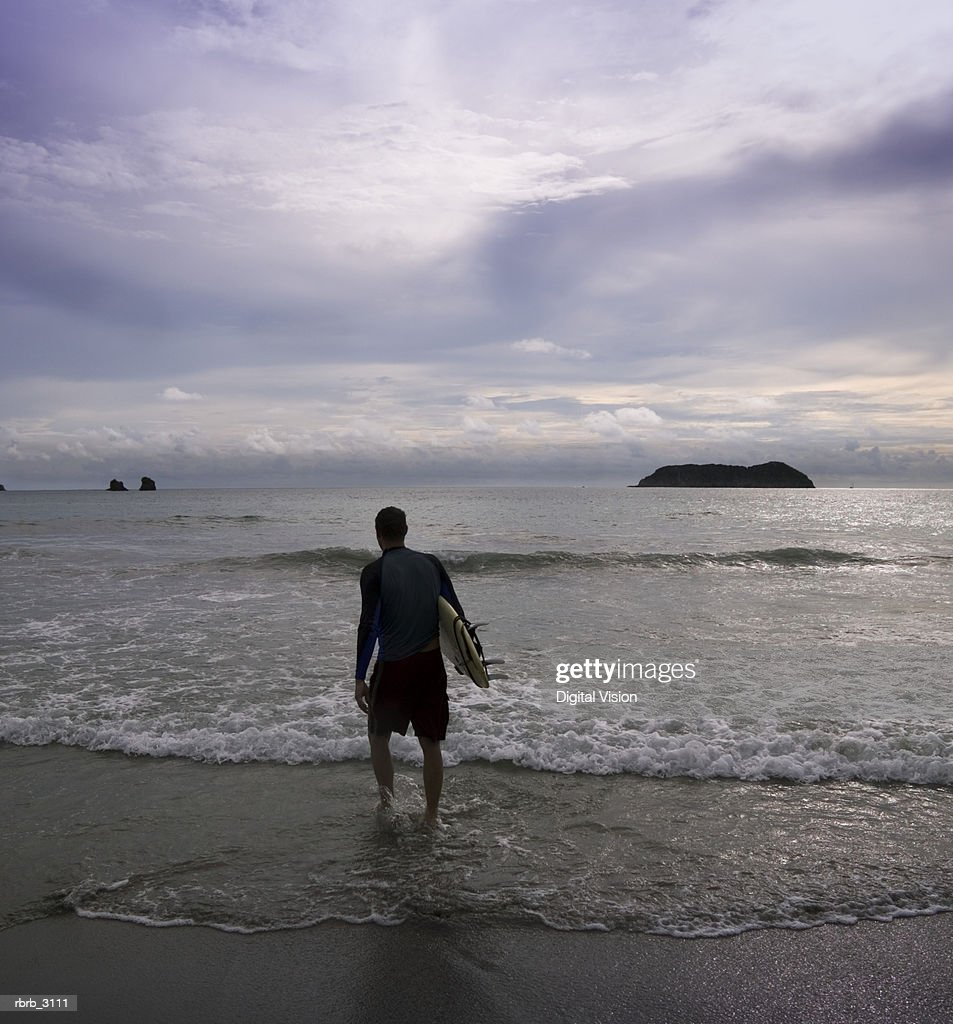 Rear view of a man with a surfboard walking towards the ocean : Foto de stock