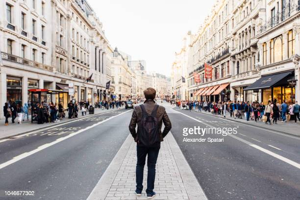 rear view of a man with backpack exploring street of london, england, uk - high street stock pictures, royalty-free photos & images
