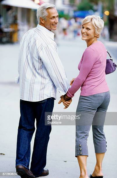 Rear view of a mature couple walking and holding hands