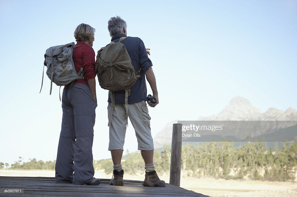 Rear View of a Mature Couple Wearing Backpacks : Stock Photo