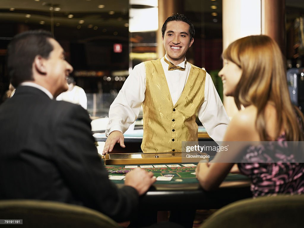 Rear view of a mature man and a young woman sitting at a gambling table with a casino worker smiling in front of them : Stock Photo