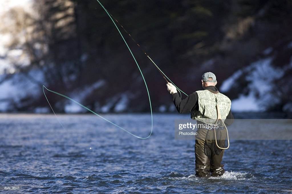Rear view of a mature man fly-fishing in a river : Foto de stock