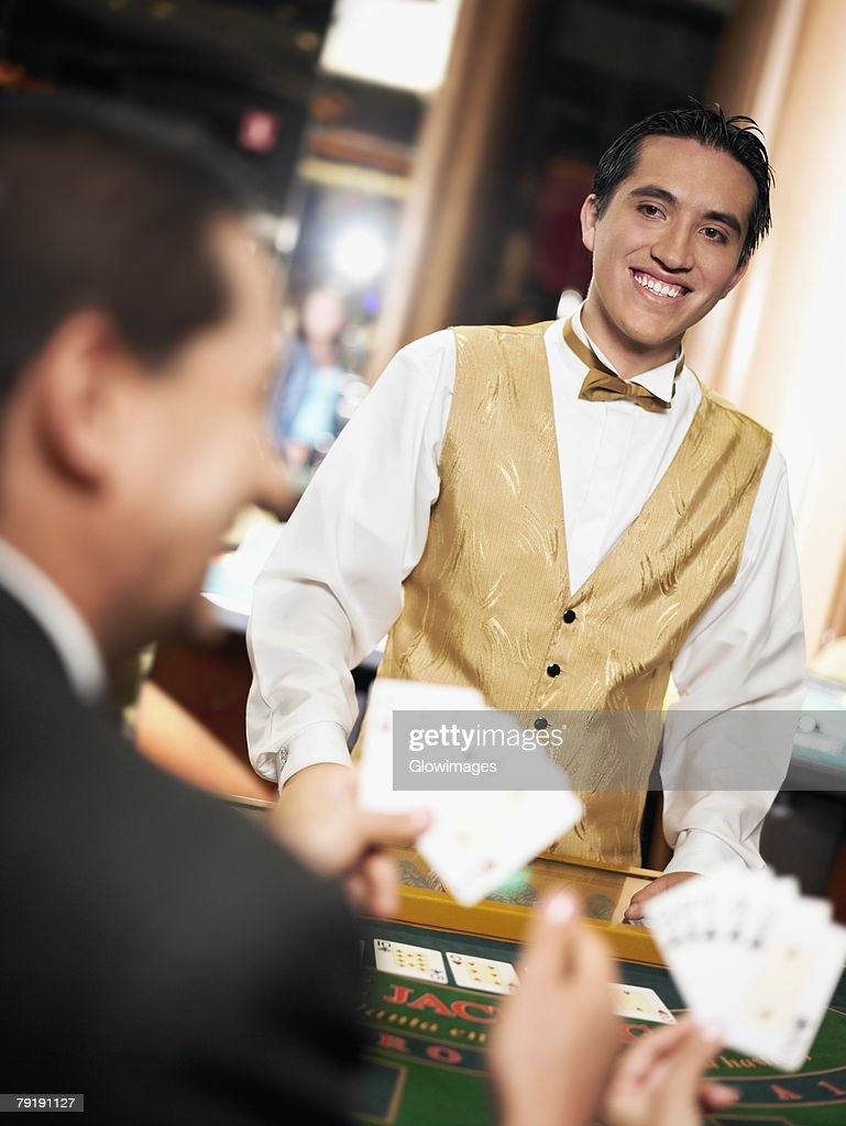 Rear view of a mature man holding playing cards with a casino worker standing in front of him : Stock Photo